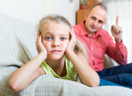 offence: Serious father 30s rebuking small daughter for offence at home Stock Photo
