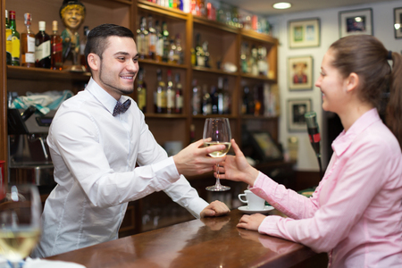 bartenders: Smiling female drinking wine at counter and chatting with bartenders.  Focus on man Stock Photo