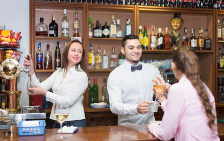 bartenders: Woman drinking wine at counter and chatting with bartenders.  Focus on man Stock Photo