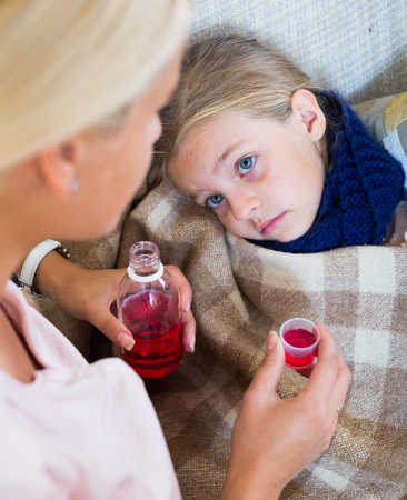 tonsillitis: Concerned mother giving mixture to daughter with cough Stock Photo
