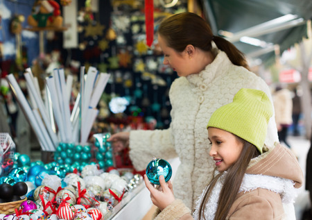 overspending: Smiling little girl with mom in Christmas market. Focus on girl