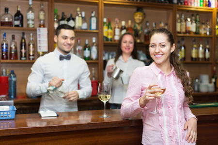 bartenders: Positive female drinking wine at counter and chatting with bartenders