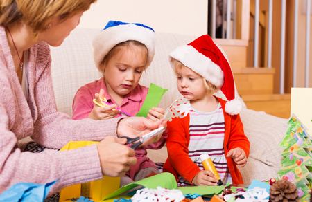 flay: Happy woman with two daughters preparing for Christmas