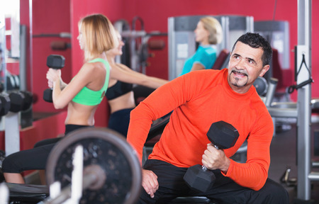 anaerobic: Active positive smiling people  weightlifting training in modern health club Stock Photo