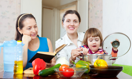 three generations of women: Happy women of three generations  cook with cookbook in the kitchen at home