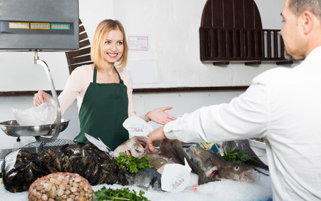 fishery: Smiling female seller in apron weighing chilled fish for customer in fishery