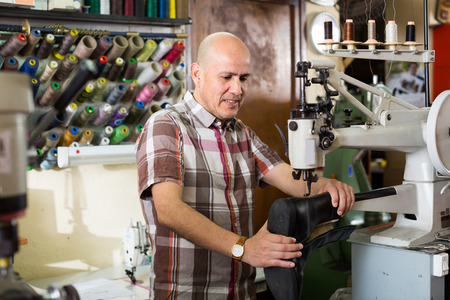 broaching: Elderly specialist stitching shoes on leather sewing machine at factory