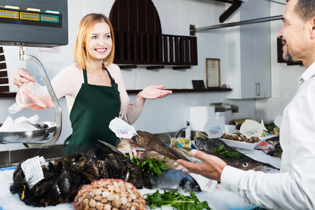 fish selling: Positive female shop assistant selling fresh fish and chilled seafood Stock Photo
