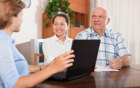 outreach: Mature couple answer questions of outreach worker with computer in home