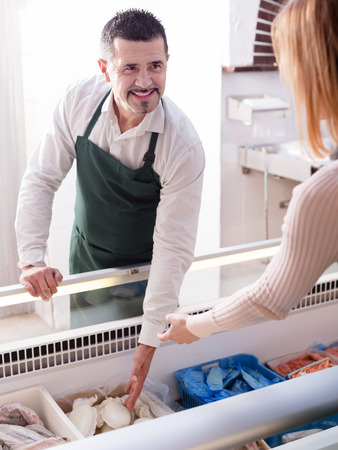 frozen fish: Adult salesman helping young woman to choose frozen fish