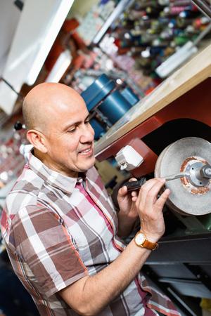 sharpening: Portrait of elderly specialist sharpening steel knife on  wheel lathe