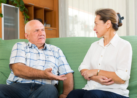 2 50: mature couple having serious talking in home interior. Focus on man Stock Photo