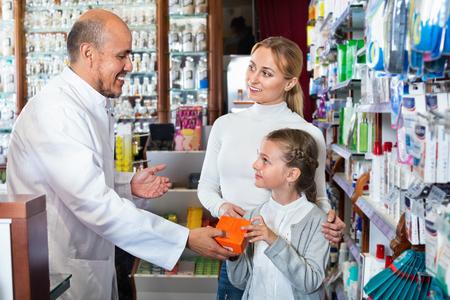 diligente: Madura de la mujer diligente farmacéutico de sexo masculino en la capa blanca que trabaja la tienda farmacéutica y la consulta de los clientes