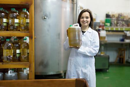 diligente: Retrato de hembra positivo diligente posando con los envases de aceite de oliva dentro de la f�brica