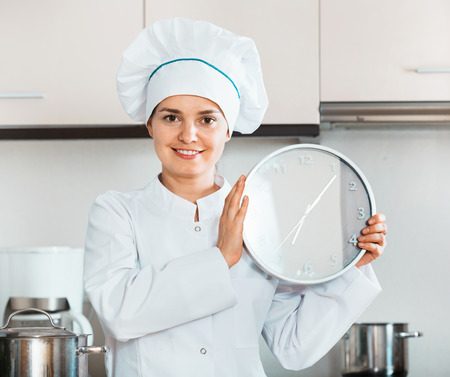 checking ingredients: Portrait of  young professional chef holding big clock