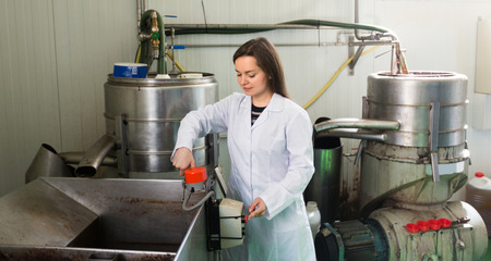 full metal jacket: Brunette young woman near oil bottling machine in manufacturing environment Stock Photo