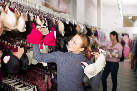 silky lingerie: Attractive young girl choosing sexy silky bra in lingerie shop Stock Photo