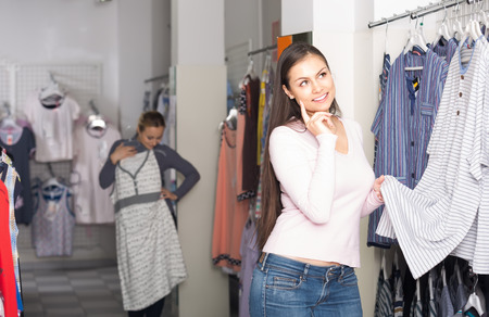 underclothing: Satisfied young woman choosing pajamas top for man in shop with underclothing
