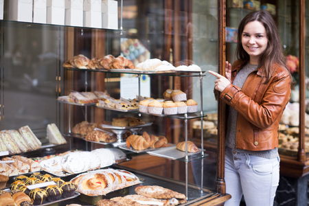 fancy cakes: Portrait of happy young brunette looking at fancy cakes in bakery Stock Photo