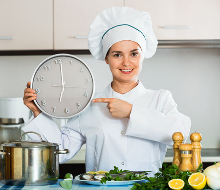 checking ingredients: Portrait of smiling young professional chef holding big clock Stock Photo