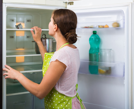 refrigerator kitchen: Starving young housewife searching food on refrigerator shelves in kitchen