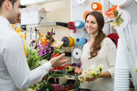 flower seller: Happy woman seller helping to pick floral bouquet of flowers man at flower shop Stock Photo