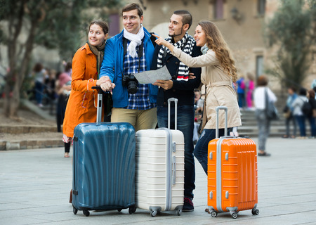 group direction: Group of friends with a luggage checking direction in a map outdoor Stock Photo