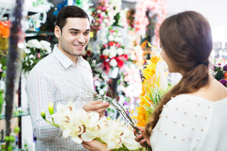 flower seller: Woman seller helping man to pick floral bouquet of flowers at flower shop