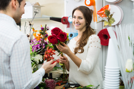 seller: smiling woman seller offering flowers male client