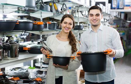 utensilios de cocina: sonriente pareja elige sartenes en la tienda de utensilios de cocina Foto de archivo