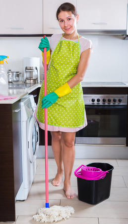 charwoman: Smiling brunette with mop and bucket in domestic interior