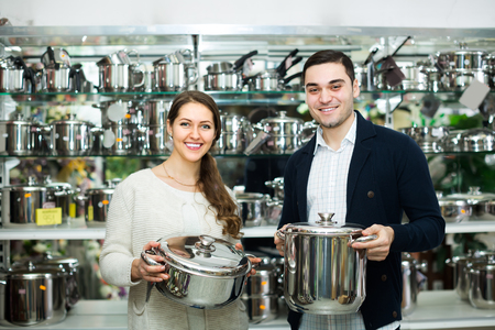 utensilios de cocina: Smiling young couple choosing new pans for home kitchen in shop cookware. Focus on man
