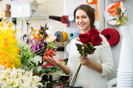seller: Woman seller helping to pick floral bouquet of flowers Stock Photo