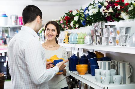 utensilios de cocina: Pares positivos que la compra de vajilla de cer�mica en la tienda de utensilios de cocina Foto de archivo