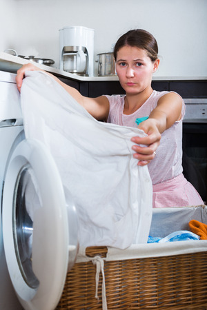 Upset adult housewife cannot wash stains off white shirt