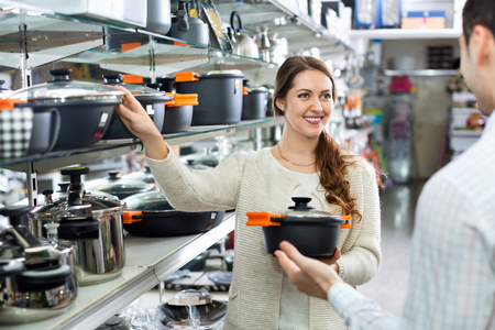cookware: Smiling positive couple in the cookware section at hypermarket Stock Photo