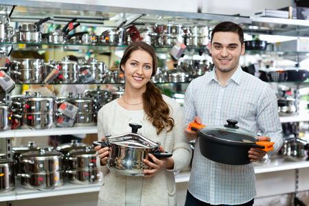 utensilios de cocina: pareja joven linda en la secci�n de utensilios de cocina en el hipermercado
