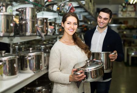 utensilios de cocina: adulto feliz pareja elige sartenes en la tienda de utensilios de cocina Foto de archivo