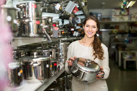 utensilios de cocina: Mujer joven en la secci�n de utensilios de cocina en el hipermercado Foto de archivo