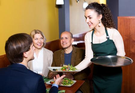 middle class: la gente de clase media que disfruta de la comida, camarera feliz teniendo orden. Centrarse en la camarera