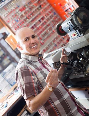 duplicate: Joyful mature workman making duplicates of keys on laser machine