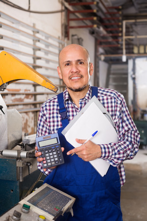 work workman: Portrait of cheerful smiling workman in coverall at the work in PVC shop