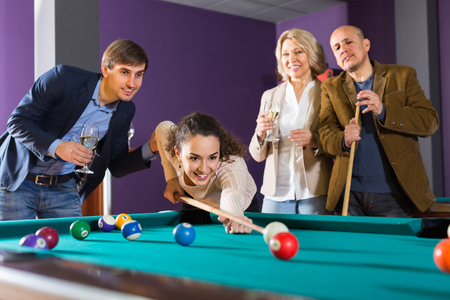 middle class: gente de clase media positivos que tienen piscina juego en el club de billar juntos