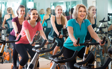 women working out: happy russian elderly and young women working out hard in sport club