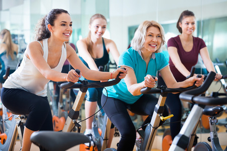 women working out: Pleasant elderly and young women working out hard in sport club