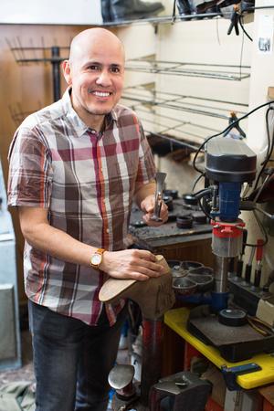 footwear: Professional shoemaker heeling footwear on machine in workshop Stock Photo