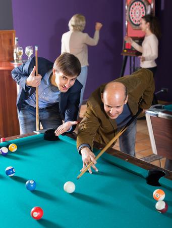 clase media: Sonriendo gente de clase media que tienen piscina juego en el club de billar