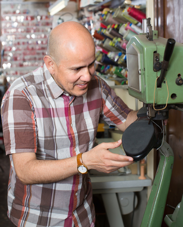 stitching machine: Smiling mature repairman stitching footwear on machine in shoe atelier