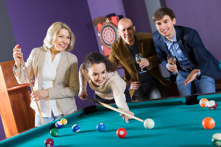 snooker cue: Mature middle class people having pool game in billiard club