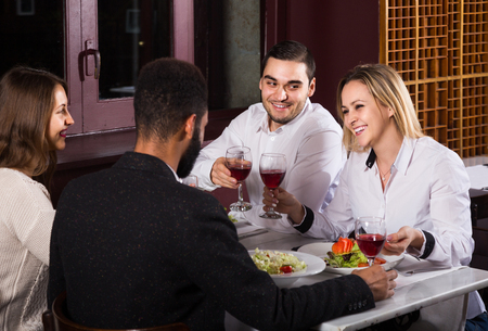 middle class: smiling middle class american people enjoying food in cafe and talking
